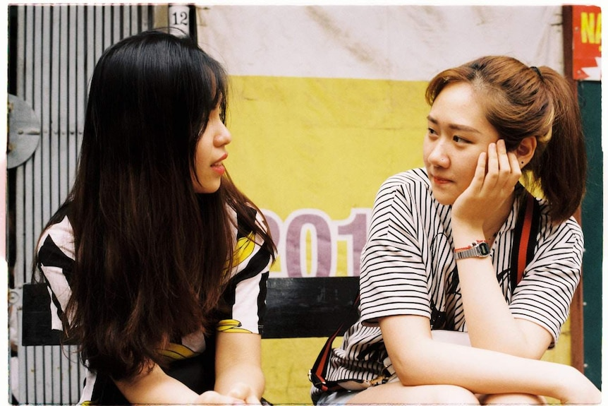 Two women sitting down next to each other and conversing to depict a story about the art and science of conversations.