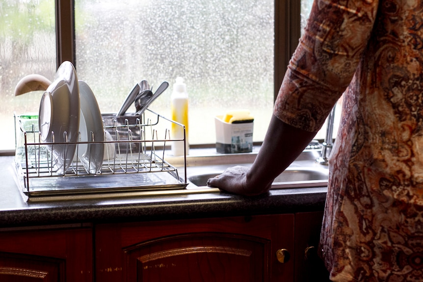 A midshot of a woman (unidentifiable) from behind leaning against a kitchen sink.