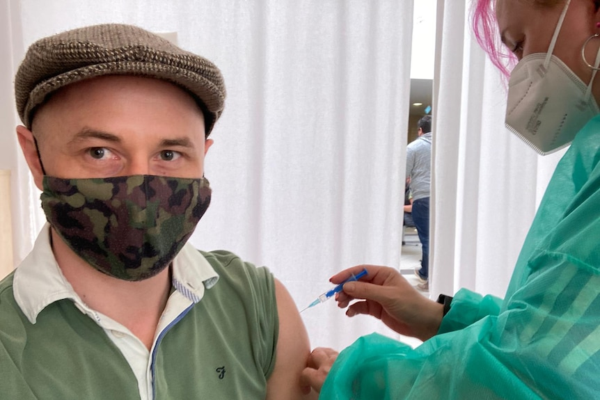 A man wearing a hat and mask receives a vaccine from a nurse with pink hair.