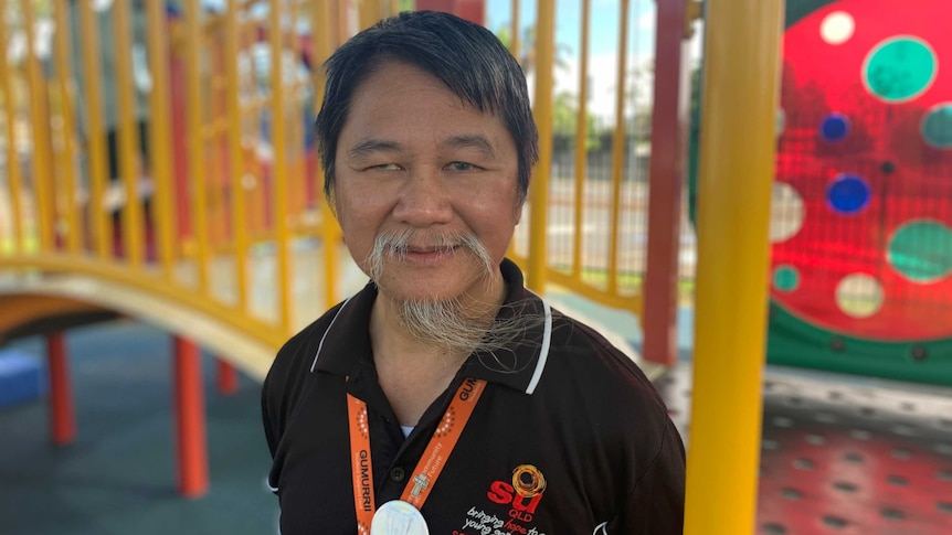 School chaplain Long Bradley smiling in front of bright school playground equipment