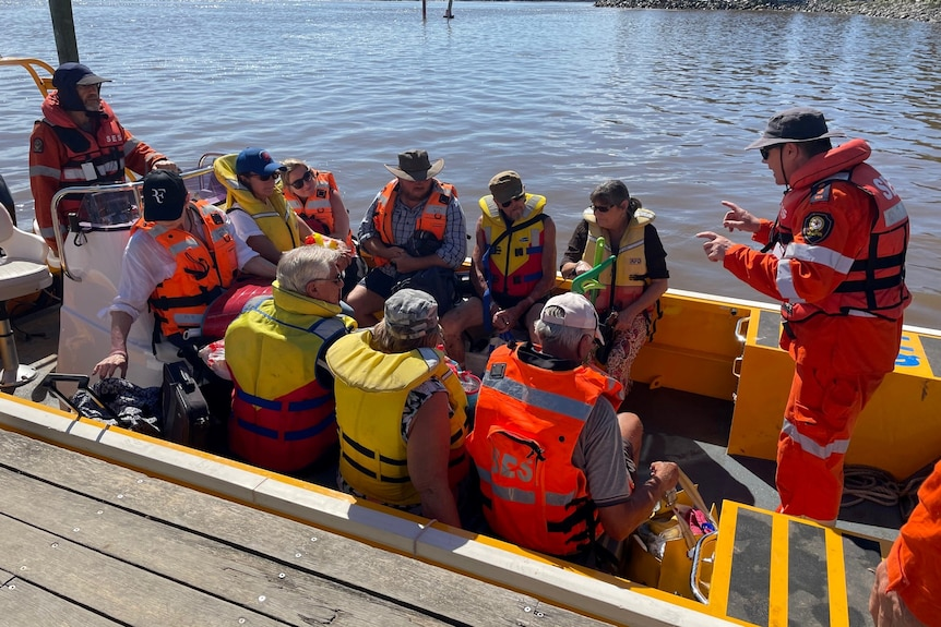 People wearing life vests sitting in small boat