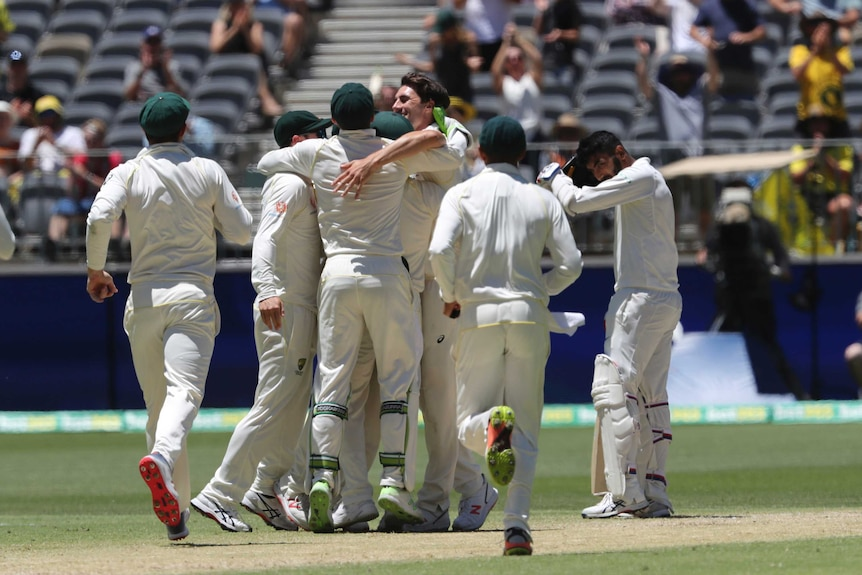 Australian players hug each other as they celebrate beating India, while Mohammed Shami looks on.
