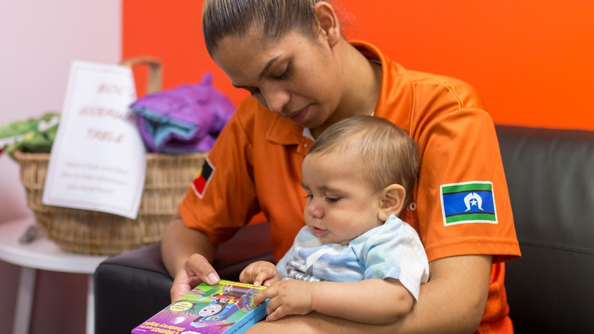 An Indigenous mother and her baby, who is holding a book, sitting on a lounge.