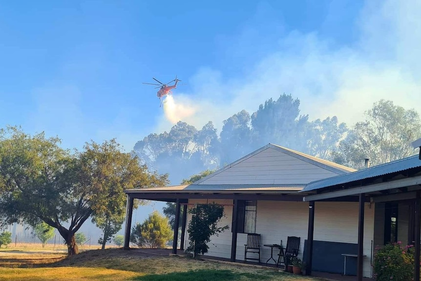 A water bomber drops its load on a fire burning close to homes