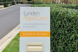 The driveway to an aged care village with the sign Lynden Aged Care at the entry in white, black and yellow.