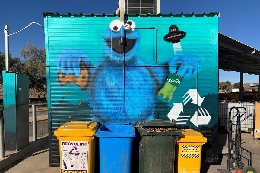 Wall mural of Cookie Monster holding chocolate chip cookie and sprite bottle. Four binsin front of the wall.