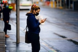 A woman wearing a face mask looks at her phone.