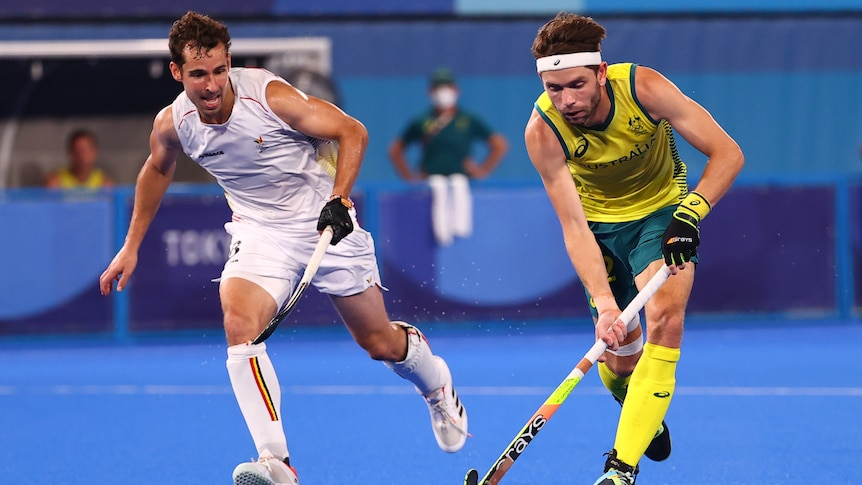 An Australian male hockey player controls the ball with his stick as a Belgian opponent runs alongside him.