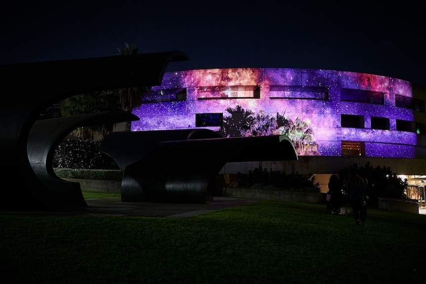 A projection by the artists Maree Clarke and Mitch Mahoney on a purple cosmos onto Hamer Hall