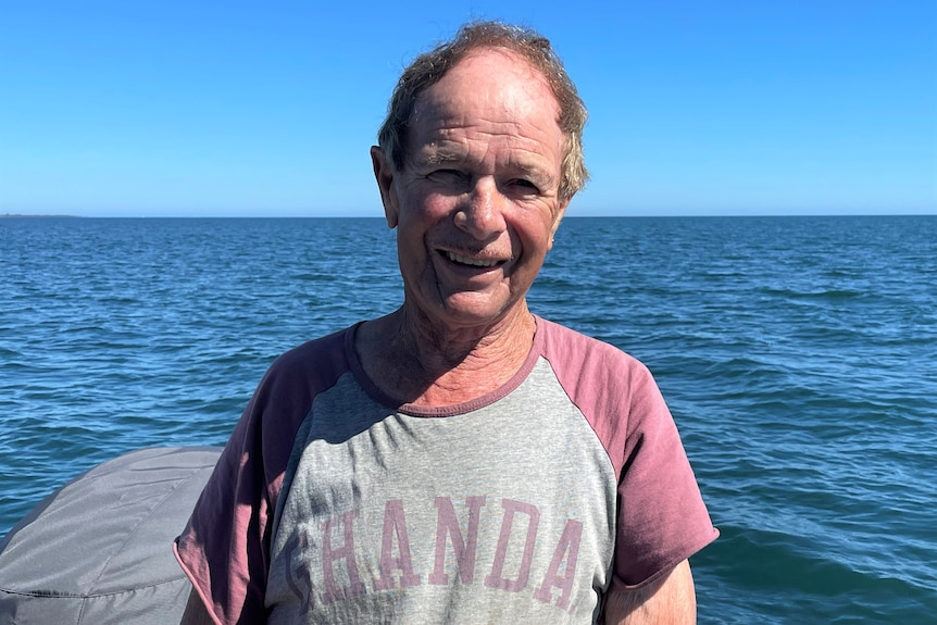 A man stands in a red and grey t-shirt, smiling at the camera. Behind him is the ocean on a sunny day.