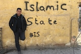 Matt Brown leaning against bullet-ridden wall painted with Islamic State #IS graffiti.