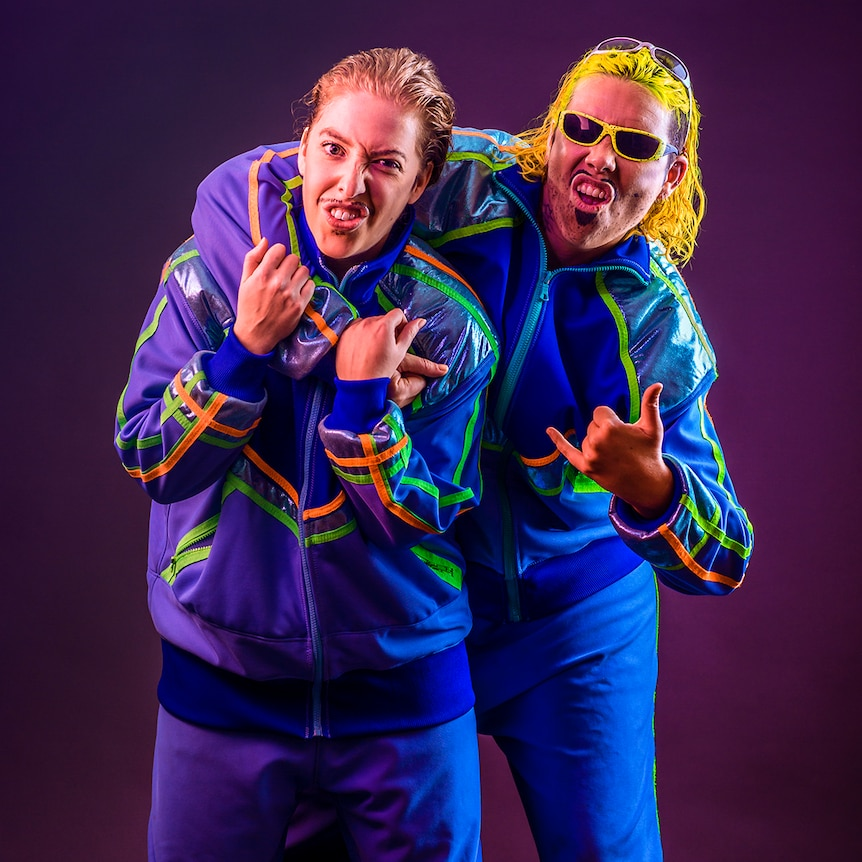 Drag characters Dazza and Keif pose in matching tracksuits.
