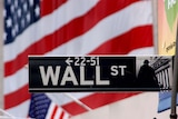 Wall Street sign with the American flag on the New York Stock Exchange behind
