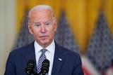 US President Joe Biden speaks while standing in front of several American flags