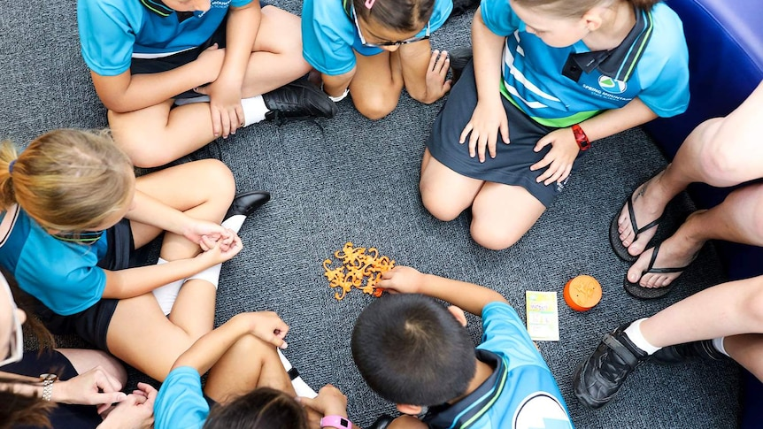 New prep-aged children sit on floor in circle in prep classroom playing barrel of monkeys game