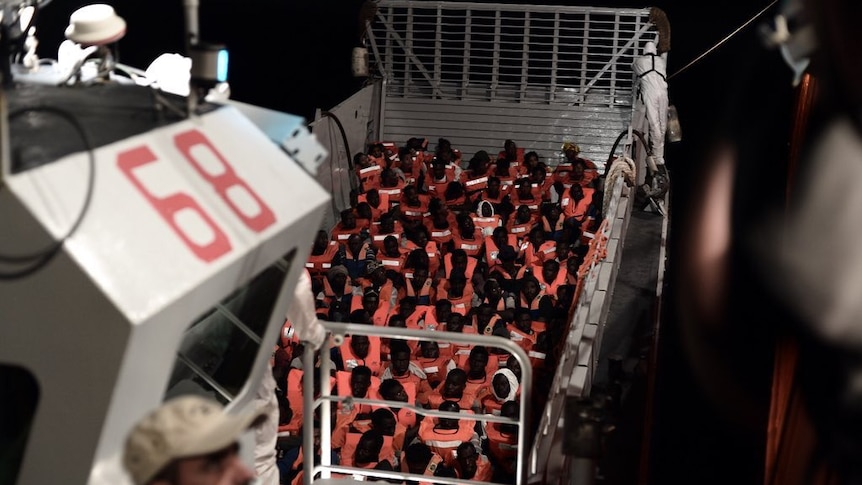 A large group of asylum seekers in life vests sit in a boat after being rescued from the sea.