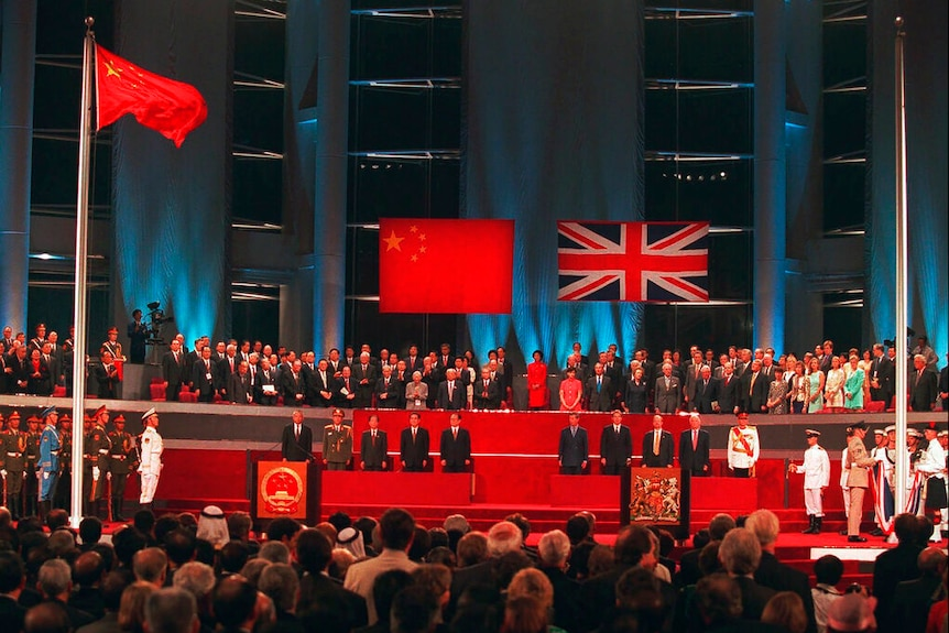 Among a crowd, you look up at a stage with Chinese and British dignitaries as British soldiers lower the Union Jack.