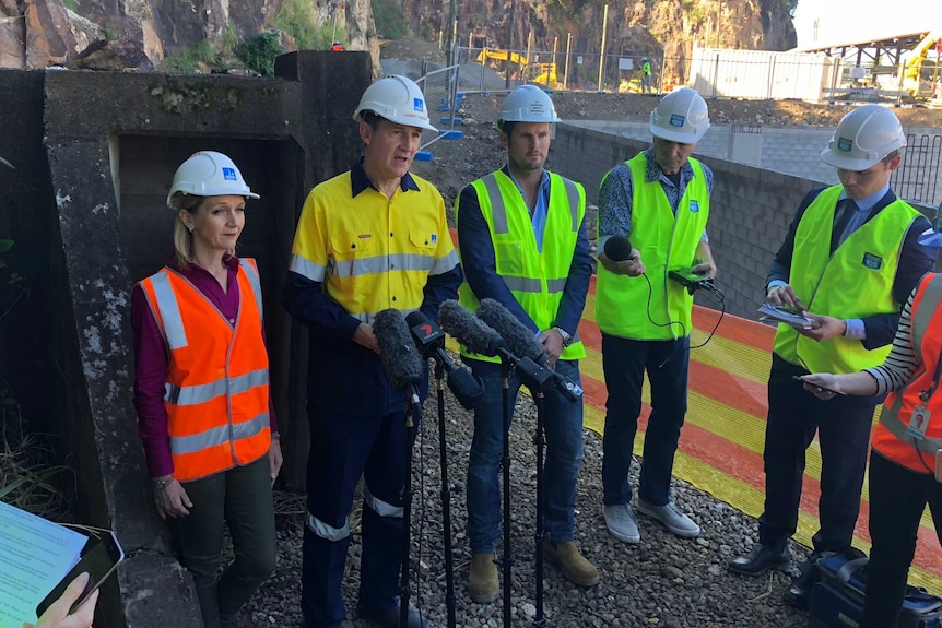 People in hard hats and high-vis vests talk to media