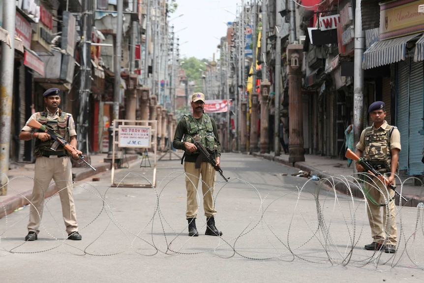 Three armed officers standing behind barbed wire