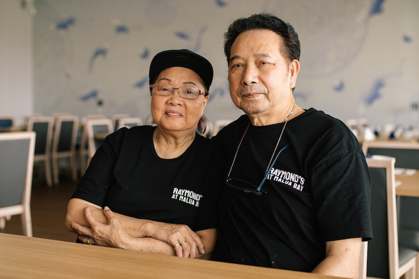A middle-aged Asian woman and man sit at a table in an empty restaurant as they pose for a photograph.