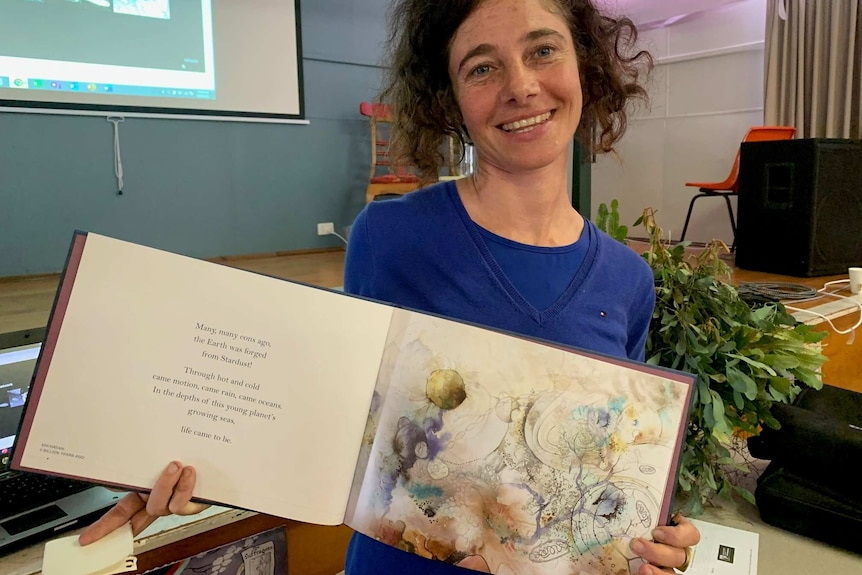Aviva Reed holding up her book of illustrations