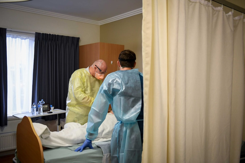 Two men in personal protective equipment stand by a patient's bed.