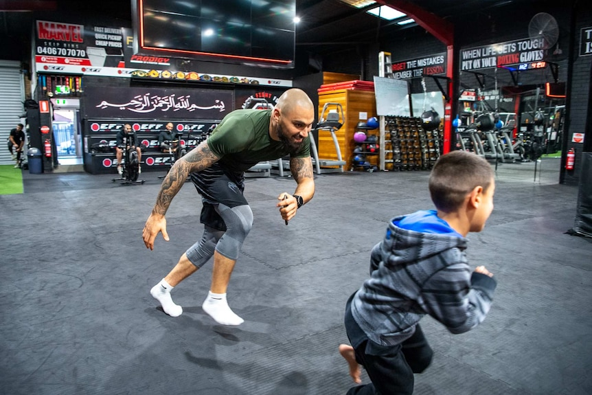 A man and child run on a mat at a gym.