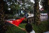 A man waves a flag next to an armoured vehicle as it drives along a civilian road past palm trees.