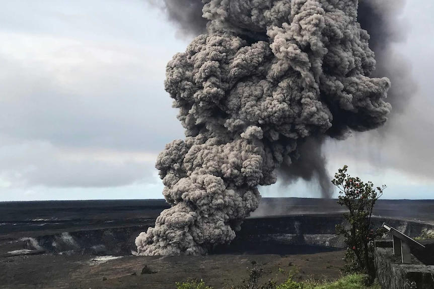 Ash column rises from the crater at Kilauea in Hawaii. It is very tall and dark.