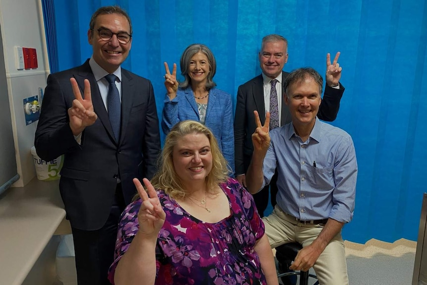 A group of people holding up two fingers as a 'V' for vaccination.