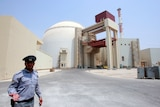 A security guard in front of a domed structure with several attached buildings.