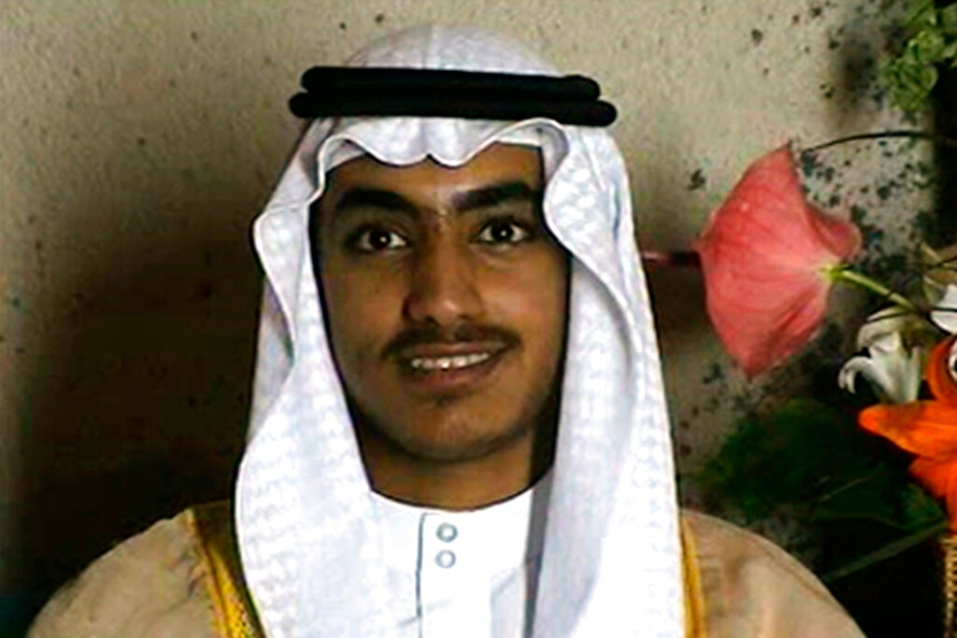 A grainy image of Hamza bin Laden in traditional dress next to a pink flower.