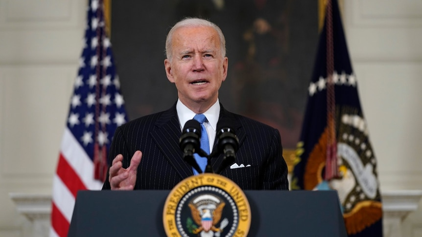 President Joe Biden speaks about efforts to combat COVID-19 from behind a podium