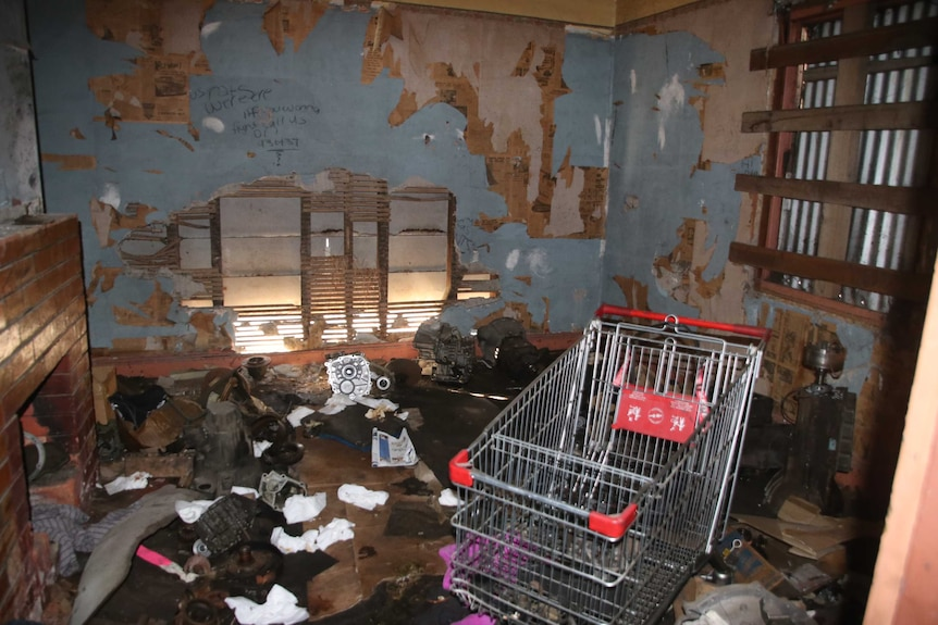 Room in derelict house with rubbish and shopping trolley.