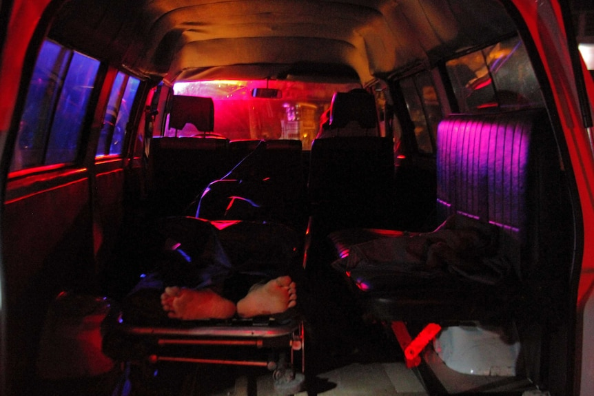 The body of Filipino meth user Carlito Gatchalian travels in the back of a mortuary service vehicle, feet visible.