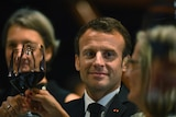 Emmanuel Macron looks as Lucy Turnbull as they toast glasses of red wine together.