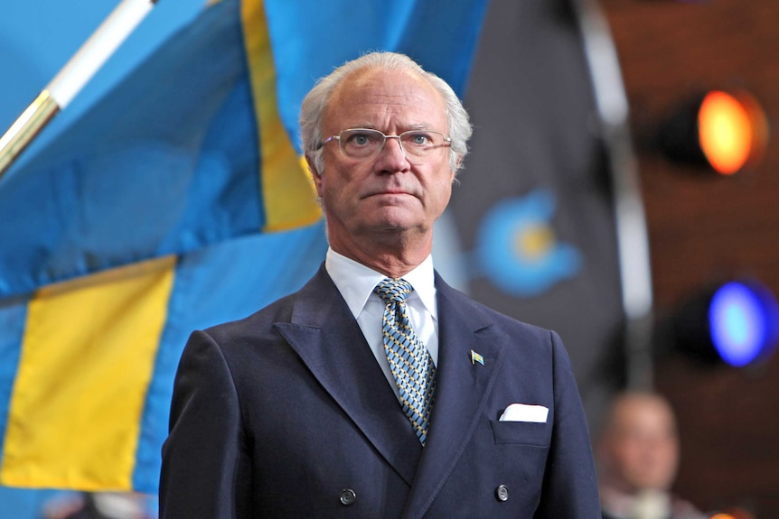 Sweden's King Carl XVI Gustaf stands in front of the national flag