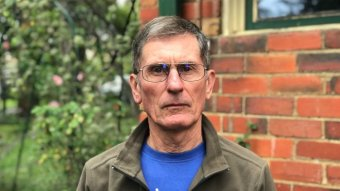 James Ashburner wears a blue t-shirt and green jacket as he stands in front of a brick home.