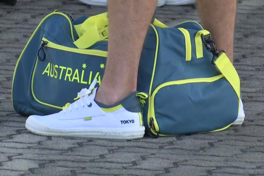Legs of an athlete with sneakers labelled Tokyo with an Australia bag