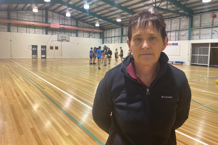 A woman in a blue jacket stands in a gymnasium, with footballers practicing behind her.