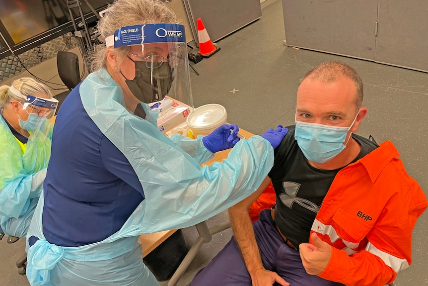 Man in fluro work gear holds thumbs up as he receives a vaccine from woman in PPE