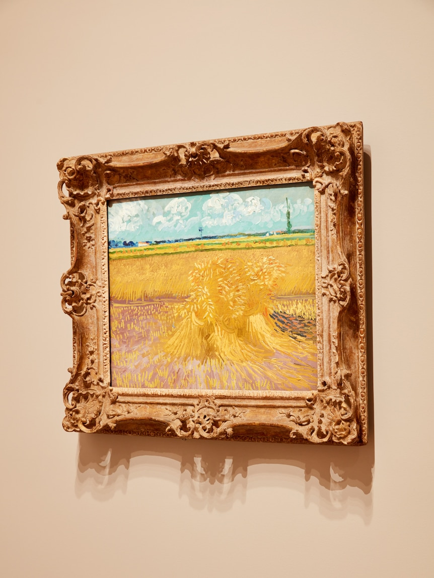 Grey wall with painting of yellow sheaf of wheat hung on it, in a gilt frame.