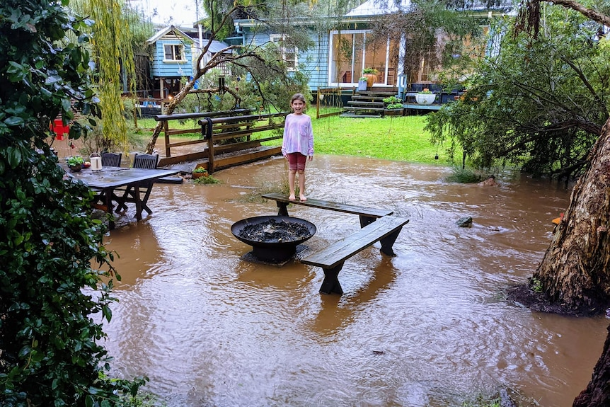 A young girl stands on an outdoor benhc in a flooded backyard with a house behind her.