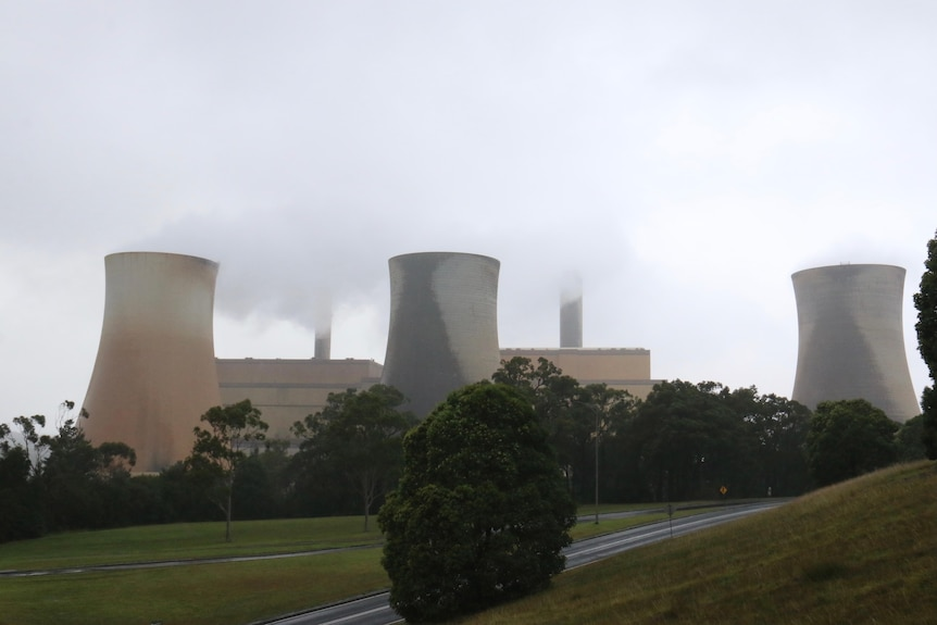 A power station with several chimneys releasing smoke