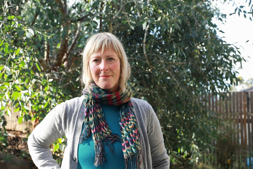 A woman wearing a green shirt, grey cardigan and multicoloured scarf stands in a garden.