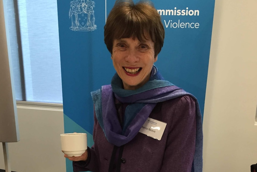 A woman with short dark hair wearing a purple jacket and scarves looks at the camera with a cup in her hand in an office setting