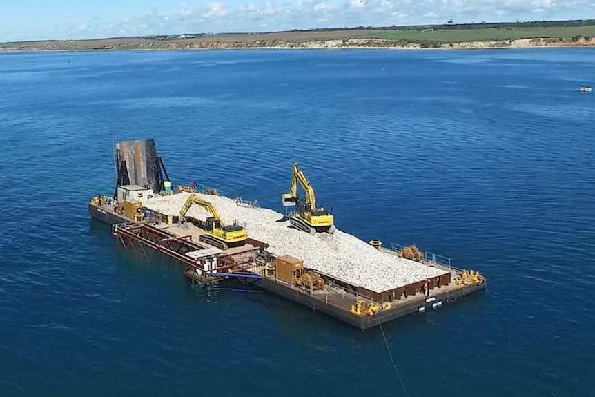 A barge with rocks and heavy machinery sits about one kilometre offshore from a sparse coastline.
