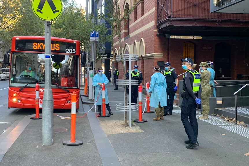 A red Skybus is parked in front of the hotel, as quarantine workers, police and army officers stand by.