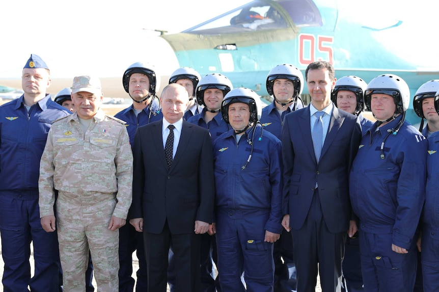 A group of politicians and air force officers pose in front of a jet fighter