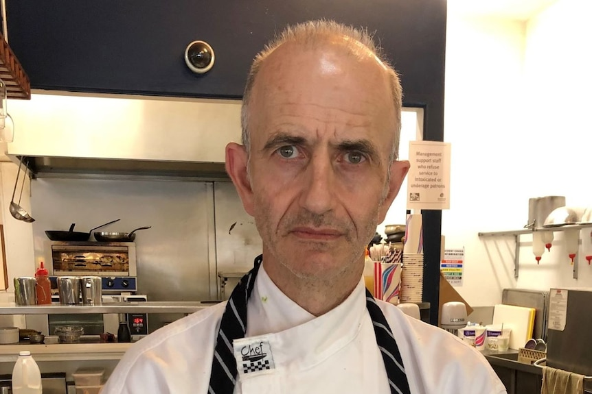 Chef in white shirt and navy apron stands in front of cluttered commercial kitchen